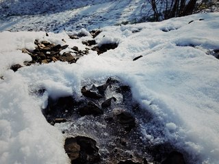 Ice and snow crust a rocky embankment.
