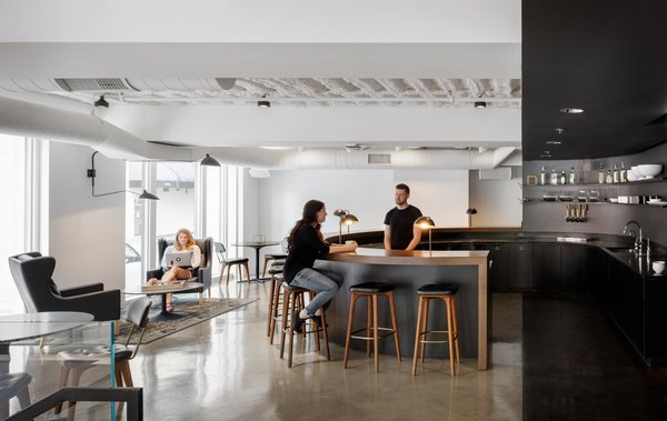 The large circular open bar and the harsh contrast of black and white make a dramatic, yet engaging, place for coworkers to congregate and connect.