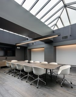 This large conference room breaks from the black and white theme to create a sea of warm neutrals flooded with natural light from above.