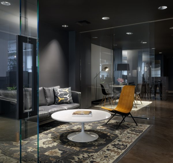 Touches of warmth are added to this dark space with dynamic lighting to breathe life into the room.