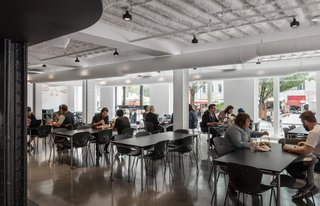 Employees eat at tables in a large entry space with plenty of windows and natural light.