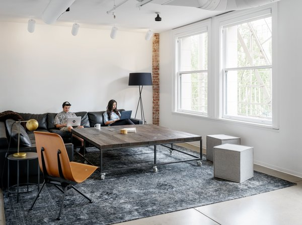 Large tables, modern plywood chairs, and neutral tones offset the white and brick to make a comfortable, open space to work in.