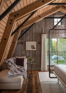 A Guest Barn in Jackson, Wyoming, Fuses Modern and Rustic Elements - Photo 2 of 7 - This living/bedroom space showcases neutral tones and shades of white to contrast the continued use of natural, treated wood surfaces.