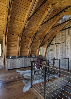 A small dining space and kitchen area blend into the expansive wood paneling used throughout The Barn.