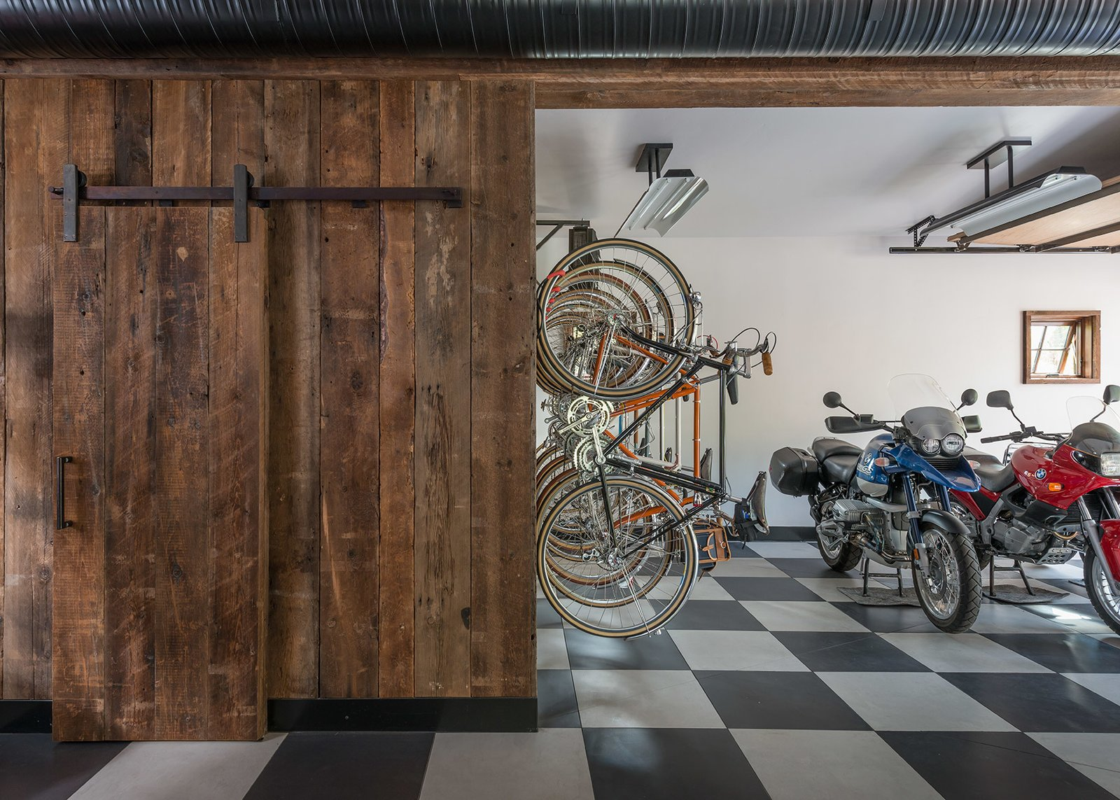 Garage and Storage Room Type This garage space uses iconic checkerboard floor tiles to contrast the rustic barn door that provides entry to the rest of The Barn.  Photo 5 of 8 in A Guest Barn in Jackson, Wyoming, Fuses Modern and Rustic Elements
