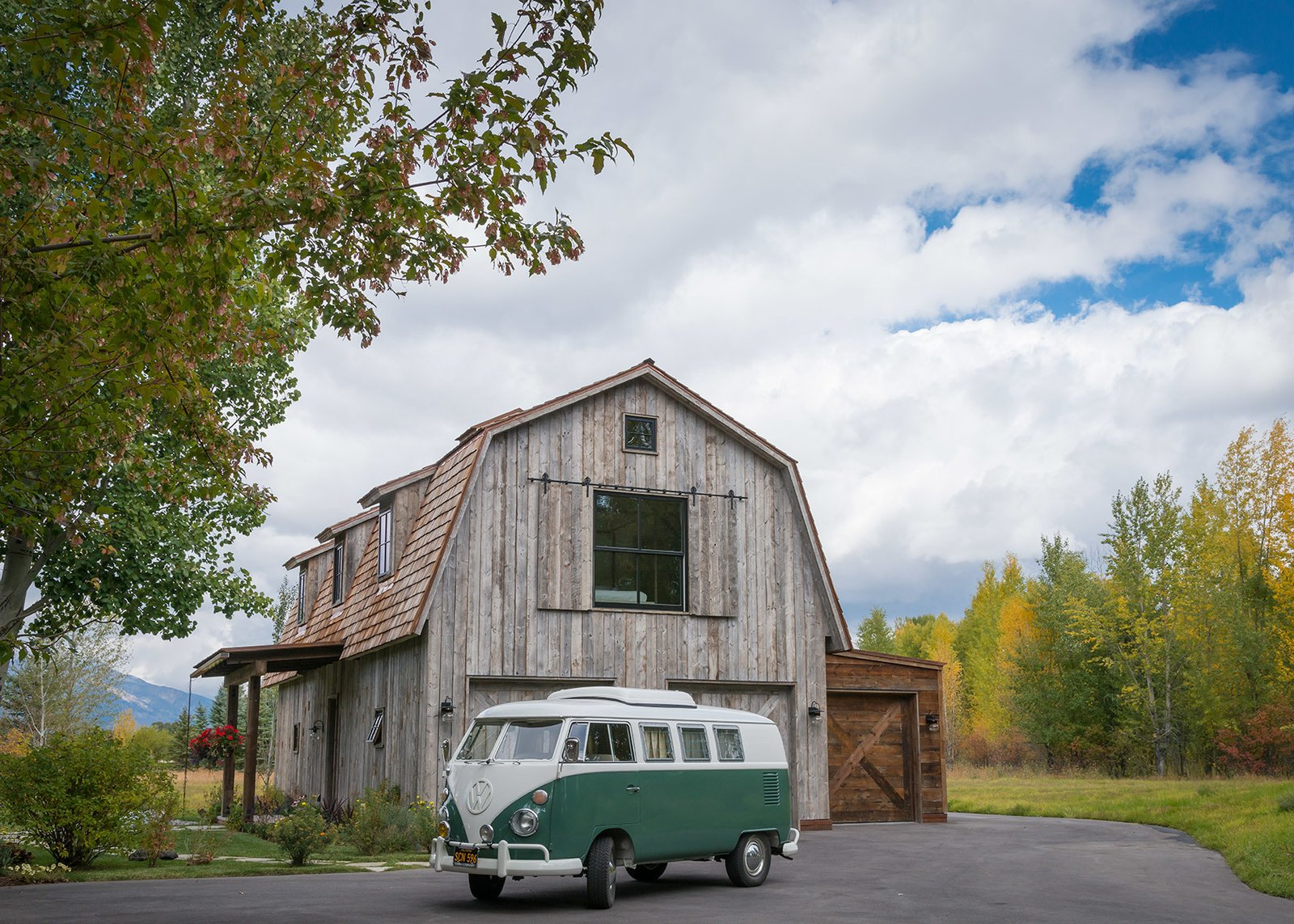 Outdoor, Side Yard, Trees, Shrubs, Flowers, Grass, Walkways, Field, and Woodland A classic VW bus in vintage colors shows both the scale and scope of The Barn and its surrounding scenery.  Photo 7 of 8 in A Guest Barn in Jackson, Wyoming, Fuses Modern and Rustic Elements