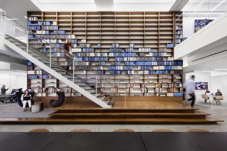 This wall of carefully arranged books at Warby Parker's NYC offices emphasizes their primary brand color in a unique way.