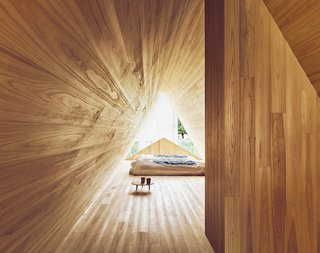 "The Community-Run Cedar House by Airbnb and Go Hasegawa Welcomes Guests in Rural Japan - Photo 10 of 12 - The bedroom space is backlit by a unique ""A"" shape that provides ample natural light—reflecting the cedar's warm, patterned tones."