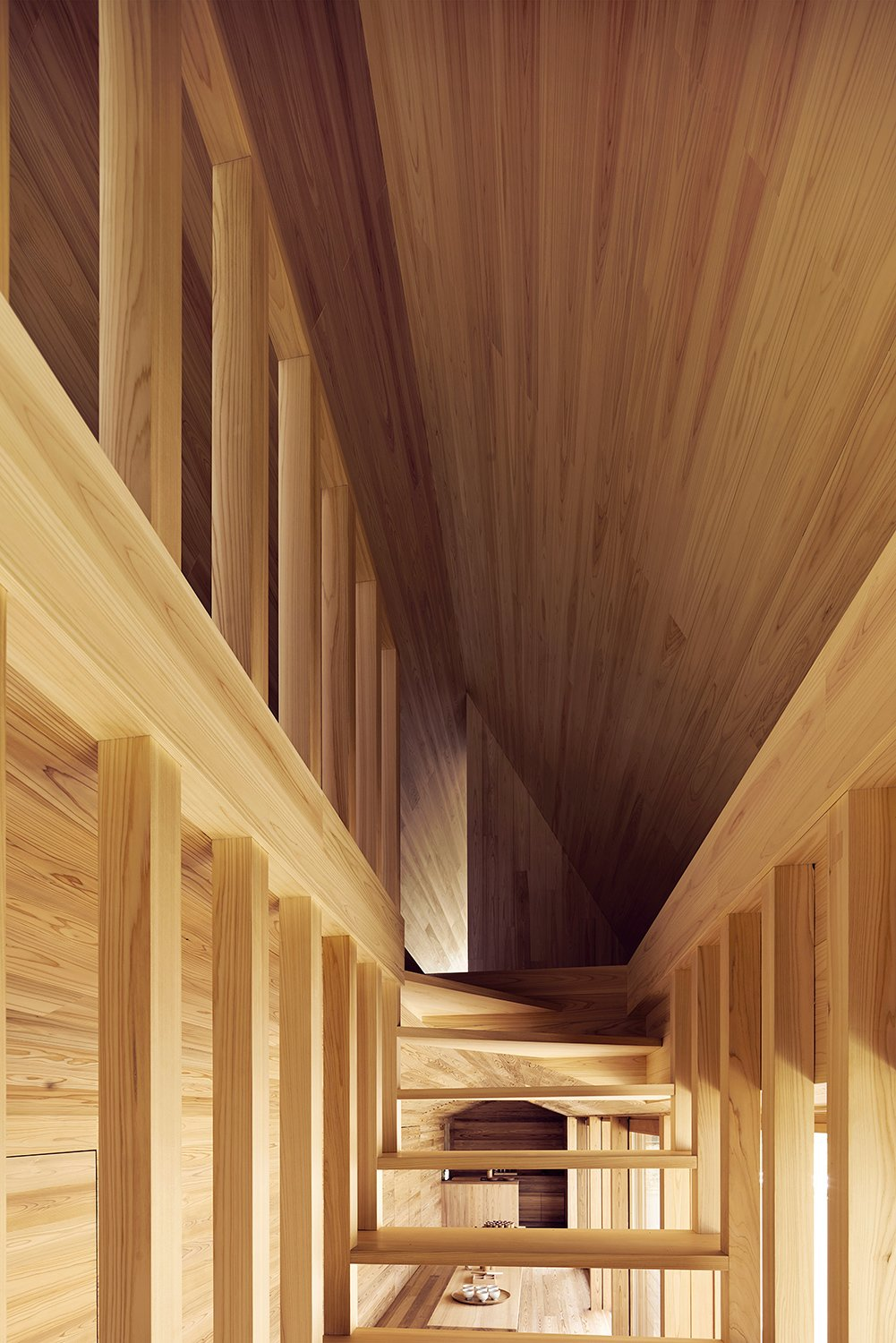The open staircase is seen from a front angle, showcasing the dynamic lines that converge at the top of the stairway leading to the bedroom space.  Photo 9 of 12 in The Community-Run Cedar House by Airbnb and Go Hasegawa Welcomes Guests in Rural Japan from Yoshino Cedar House