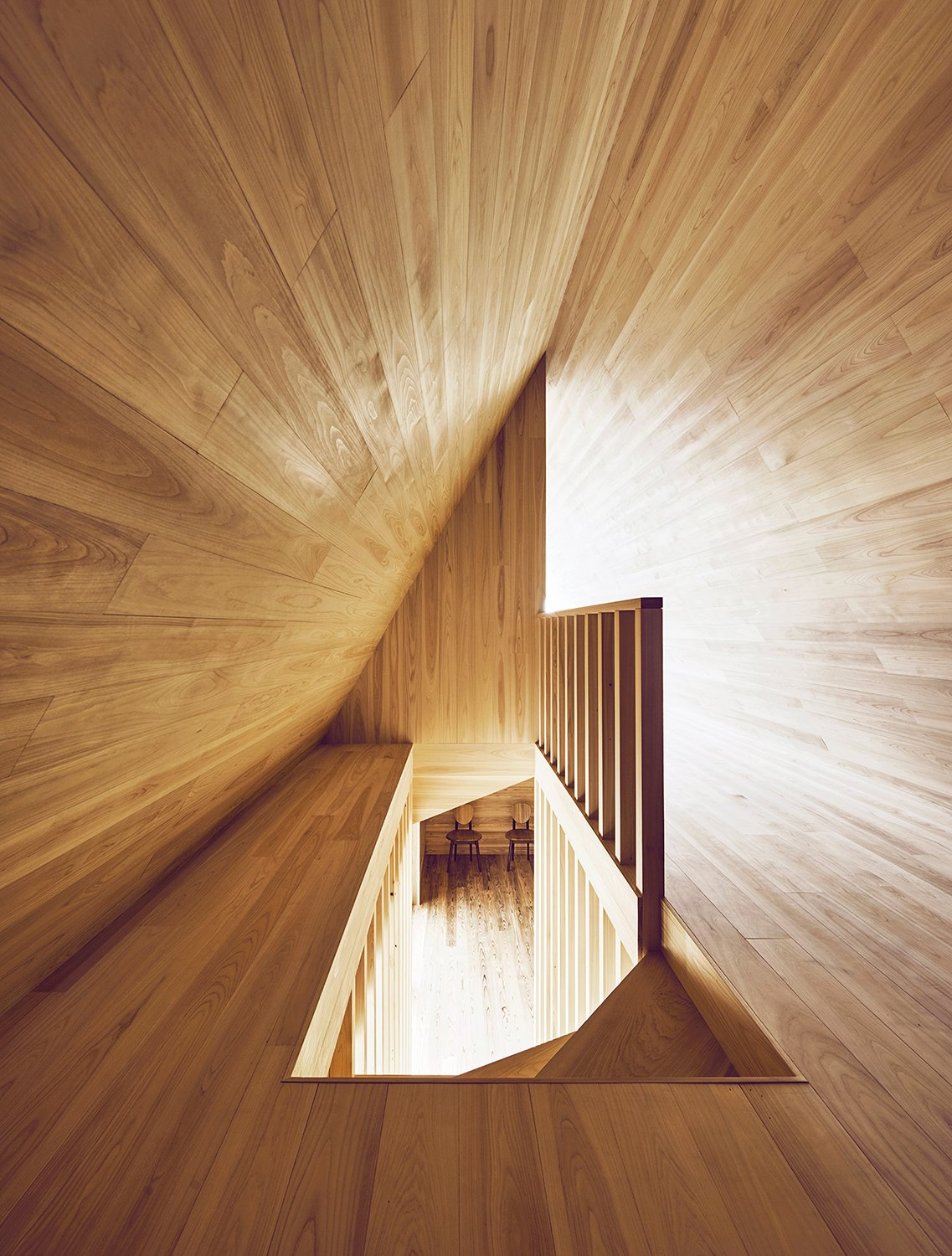 Looking down the stairway from above reveals the A shape of the upper floor and contrasting angles and tones of natural light.  Photo 11 of 12 in The Community-Run Cedar House by Airbnb and Go Hasegawa Welcomes Guests in Rural Japan from Yoshino Cedar House