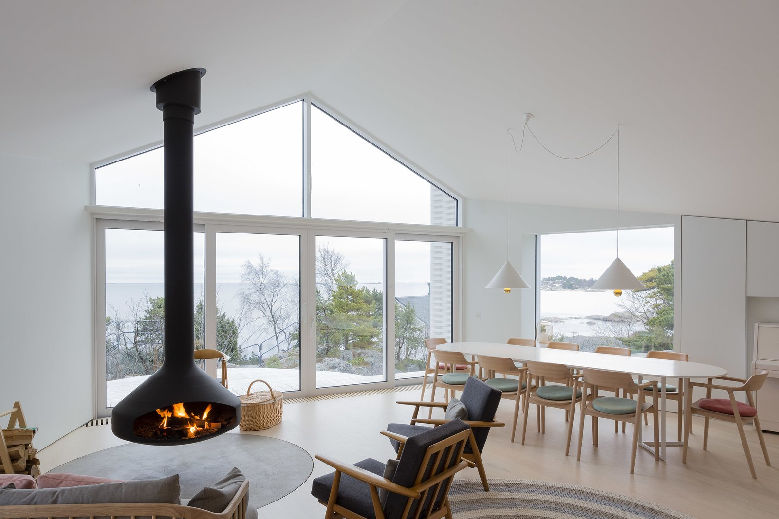 Living Room, Light Hardwood Floor, Chair, Hanging Fireplace, Pendant Lighting, and Sofa  Photo 4 of 12 in A Modern Finnish Villa That Grows Out of a Seaside Cliff