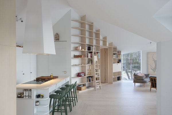 Living Room, Bookcase, and Light Hardwood Floor  Photo 8 of 12 in A Modern Finnish Villa That Grows Out of a Seaside Cliff