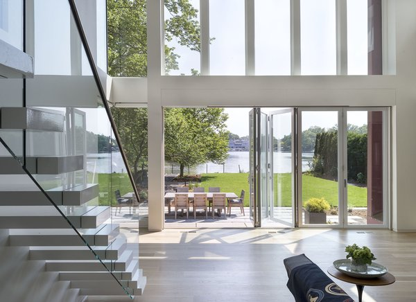 The new extension opens out dramatically onto the rear yard, which faces the river. The living space expands beyond indoors and flows outside to an outdoor deck with a large dining table.