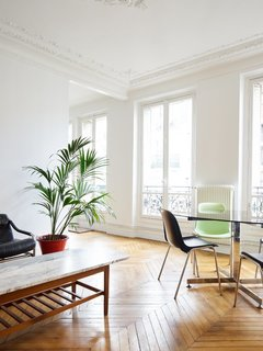 In the 11th arrondissement, the elegance of wood chevron floors, delicate crown molding, and ceiling medallions is balanced by stark white walls and ceilings and a select few pieces of furniture, allowing the white French doors and views to the outside to take priority.