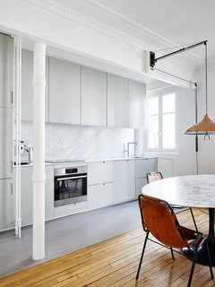 The white walls, ceilings, and decorative crown moldings continue into the kitchen area, where light gray cabinets and a medium gray floor covering highlight the marble of the tabletop and backsplash.