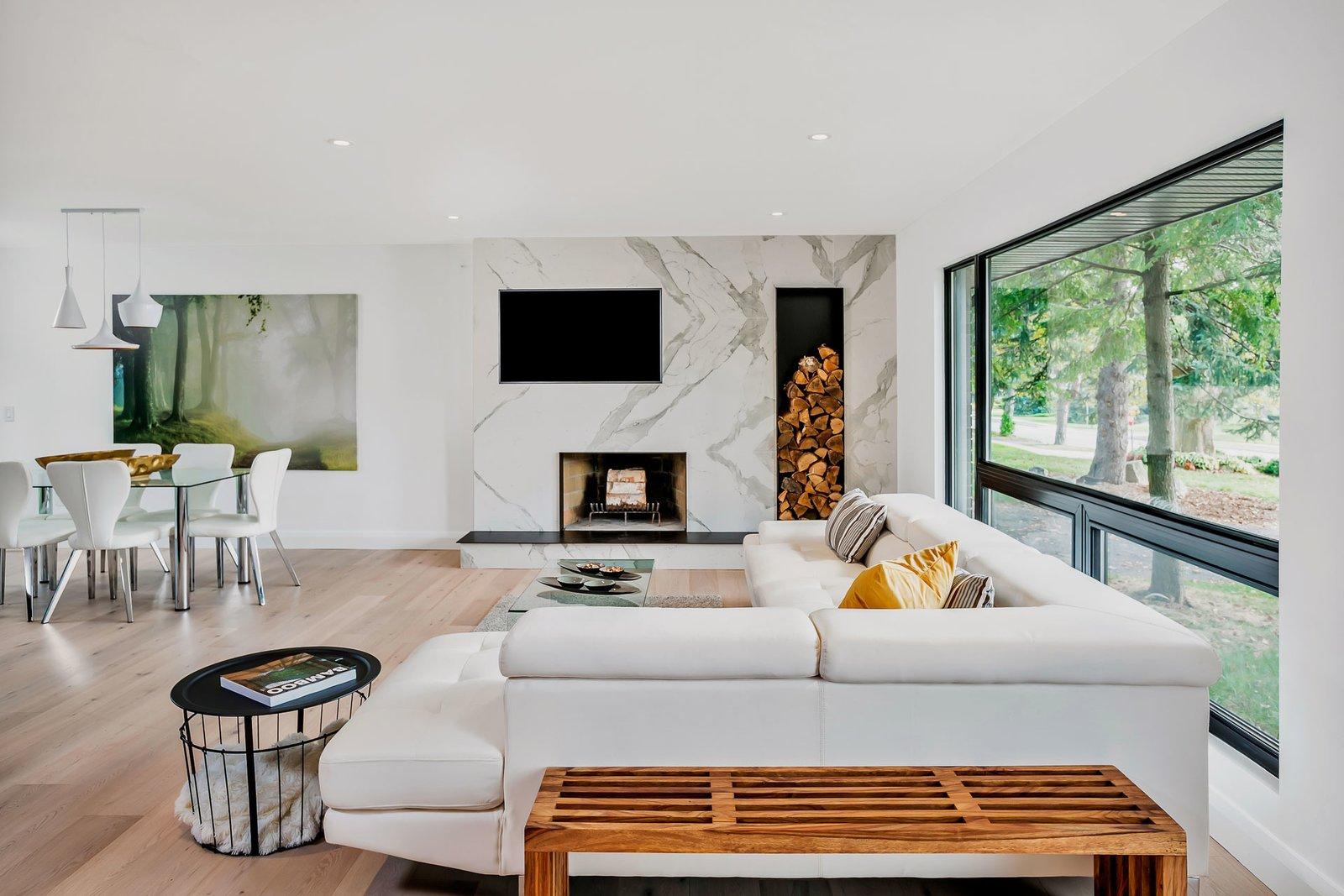 Living Room, Wood Burning Fireplace, and Light Hardwood Floor  Modern Renovation