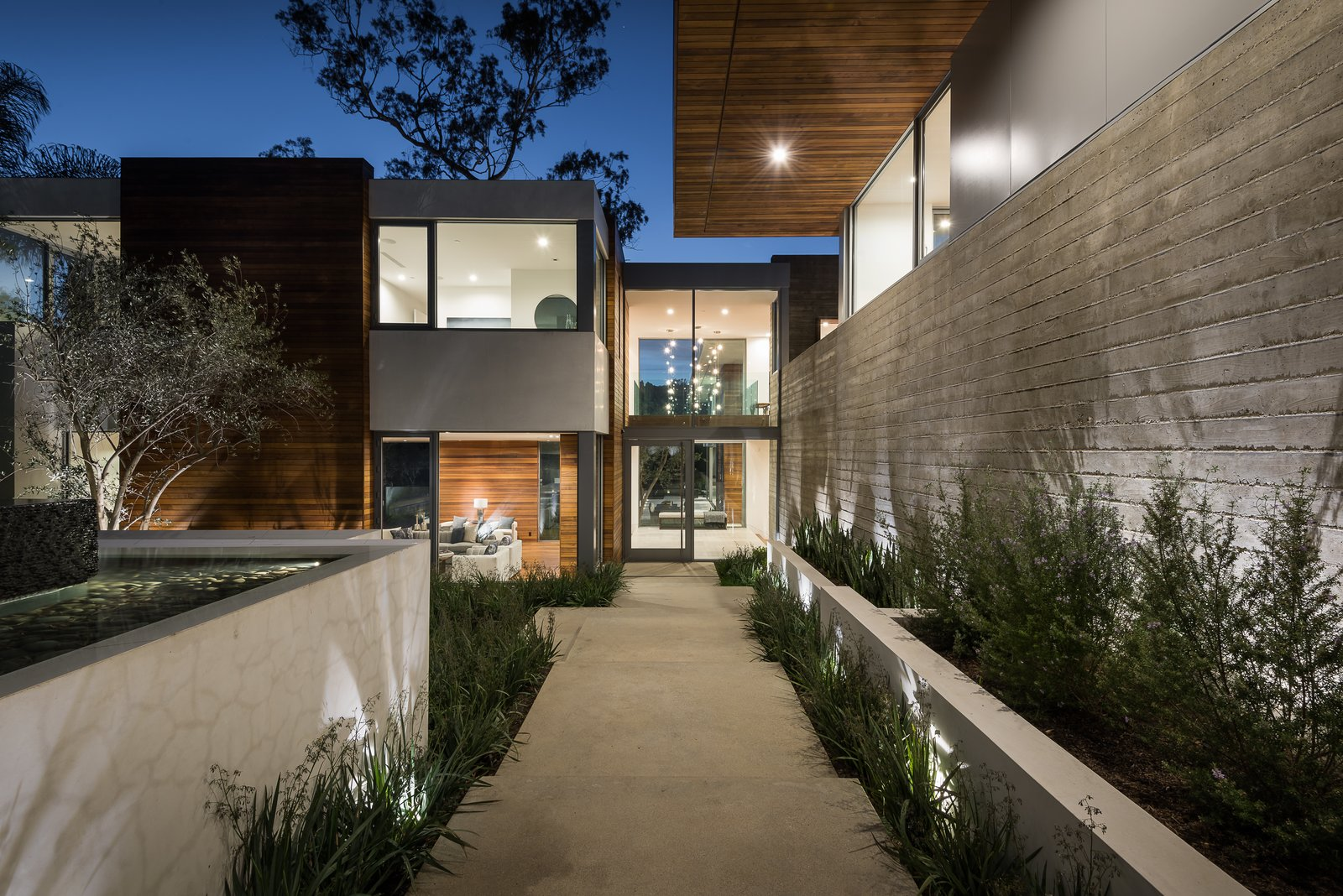 Outdoor, Walkways, Shrubs, Trees, Front Yard, Horizontal Fences, Wall, Landscape Lighting, Grass, Concrete Fences, Wall, Hardscapes, Wood Fences, Wall, and Gardens  Ravoli Drive Residence