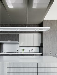 An overhead lighting fixture by ALW hangs above the island's gray/white stained engineered oak, which contrasts with the cabinet's darker gray engineered oak.