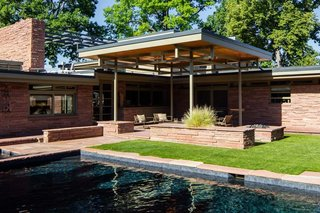 The swimming pool did not originate with the house, but<br>came about later in a 1980 design by Hans Kahn Associates,<br>Inc. The metalwork supporting the patio cover borrows<br>rhythm and form from nearby transom windows. In the<br>Hornbein-era backyard, grass and a swing set prevail, both<br>in the shadow of the second-story solarium.