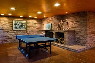 The rumpus room delighted the Kohn<br>family, with its sprawling fireplace,<br>television seating, and honed-flagstone<br>arena for ping pong—a sport the<br>current owners of One Eudora also<br>enjoy. The articulated wood figures<br>on the mantel, made for a gym in the<br>early 20th century, were used to teach<br>children how to box. The framed vellum<br>is a historic Denver-area trolley sign.