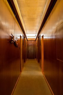 A long clerestory illuminates the hallway dividing the bedroom<br>wing of the house. The door at the end originally opened to racquet storage and<br>pathway access to a subterranean tennis court. The carved greyhound dates to<br>the 1920s.