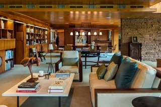 Warmth permeates the living room,<br>where Honduran mahogany paneling,<br>bookshelves and built-ins stand<br>sumptuously in concert with birch<br>ceiling tiles, all caramelized with age.<br>Jeffrey P. Elliott executed the interior<br>design, weaving in the homeowners'<br>quirky collection of art, objects and<br>furnishings—no easy task considering<br>the Marianna von Allesch glass mural<br>juxtaposed with a toy monkey shaking<br>a martini. The striped chair in the<br>background is a rare Victor Hornbein<br>commission, one of a pair. The sculptural<br>staircase seems to float in place, belying<br>its satisfying weightiness underfoot.<br>A thin metal edge inserted into the<br>hardwood tread prevents slipping<br>and beautifully punctuates the Lou<br>and Romy Bieker design.