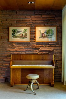 One of many custom extravagances is<br>an upright piano that Victor Hornbein<br>convinced Steinway & Sons to manufacture<br>using veneers specified for the<br>house. Hanging above are watercolors<br>that Hornbein himself painted, elegantly<br>rendering his architectural vision. An<br>accomplished artist as well as architect,<br>Hornbein executed large murals around<br>Denver under the tutelage of legendary<br>muralist Allen Tupper True.