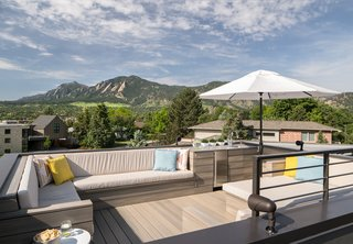 "The NewTechWood composite rooftop deck has 360-degree views that include the Front Range and downtown Boulder. ""I call the deck 'the icing on the cake,'"" said the homeowner. The custom furniture was built to be large enough to allow for easy slumber parties (for both adults and kids) under the stars."