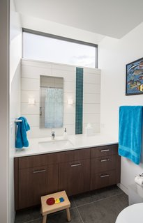 "A light-enhancing transom window in the kids' bathroom mimics the high-floating windows in the adjacent bedroom. Large-scale gray floor tiles and sleek cabinetry contrast with the playful vertical stripe in the tile (""the owners wanted a little bit of color and pop,"" says Goff); the hue mimics a teal blue seen throughout the home. Remove the children's stool, and the bath will become sophisticated enough for a teen—or beyond."