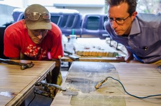 Game On - Photo 2 of 5 - Designer James Davis had been experimenting with electrical erosion for about six months before meeting Vertical Arts' Brian Patty at a networking event. They quickly devised a plan to incorporate the technique into a multi-purpose table for VA's new office space. Using a solution of baking soda and saltwater to provide a general pattern, electrical clamps run through a series of microwave transformers to create a unique design on walnut butcher block.