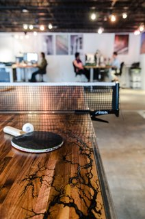 Game On - Photo 4 of 5 - Once the electrical erosion was complete, Davis sanded down the table and added wax and epoxy to create a smooth, flush surface. When it's not being used for an afternoon ping pong match, Vertical Arts employees release the table into two halves that can be used for drawing, client engagement, or impromptu breakout sessions.