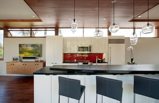 The floorplan of the home strategically places the primary living spaces including the kitchen, living room, and master bedroom on the second floor, maximizing the user's exposure to views as well as the surrounding tree canopy. Wood ceilings, floors, and window frames are paired with stark white walls and bold accent colors to juxtapose modern architectural detailing with a sense of warmth and intimacy.