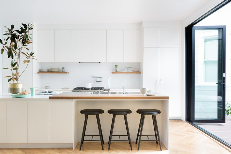 Kitchen, Light Hardwood Floor, Refrigerator, Dishwasher, Ceiling Lighting, Wood Counter, Cooktops, Wall Oven, and White Cabinet    Noe Valley Parisian Atelier by Regan Baker Design
