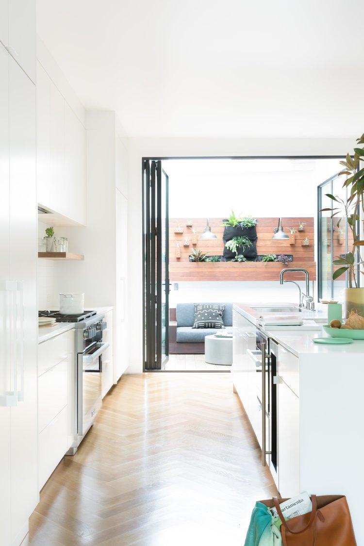 Kitchen, Dishwasher, Ceiling Lighting, White Cabinet, Light Hardwood Floor, Wine Cooler, and Wall Oven    Noe Valley Parisian Atelier by Regan Baker Design
