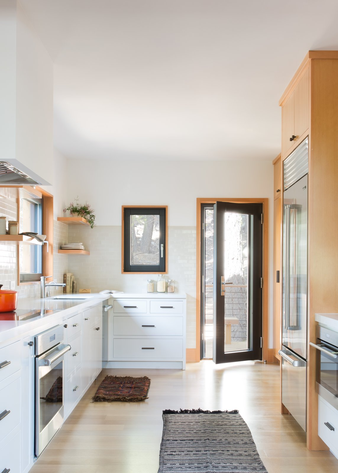 Kitchen, White Cabinet, Ceramic Tile Backsplashe, Undermount Sink, Light Hardwood Floor, and Refrigerator  Woodsy Tahoe Cabin by Regan Baker Design