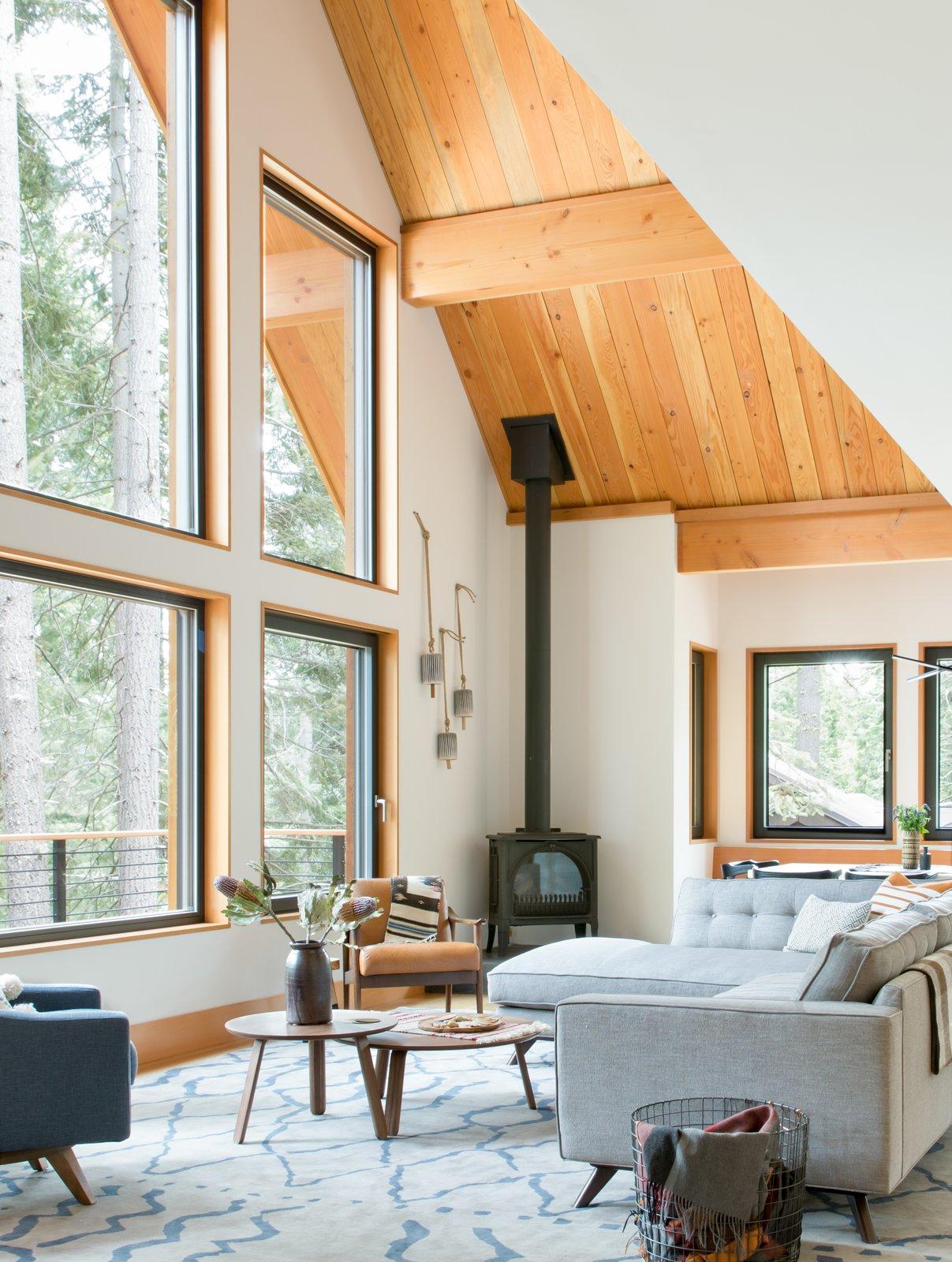 Living Room, Sectional, Corner Fireplace, Chair, Rug Floor, Light Hardwood Floor, and Wood Burning Fireplace  Woodsy Tahoe Cabin by Regan Baker Design