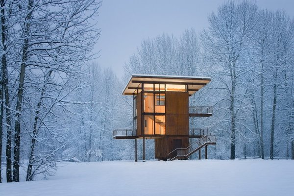 "Self-described by architect Olson Kundig Architects as ""basically a steel box on stilts,"" the three-story cabin in upstate Washington can be completely sealed off to the elements with four 10' by 18' steel shutters that can be rolled over the glass windows when visitors clear out."