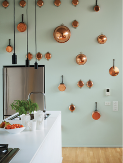A wall of artfully arranged copper pots with a contrasting paint color makes a bold statement in this small kitchen.