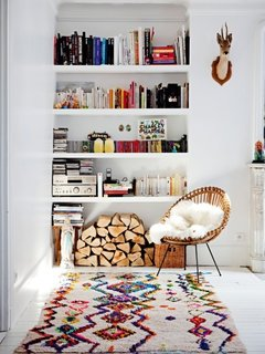 A recessed white bookshelf holds far more than just books.