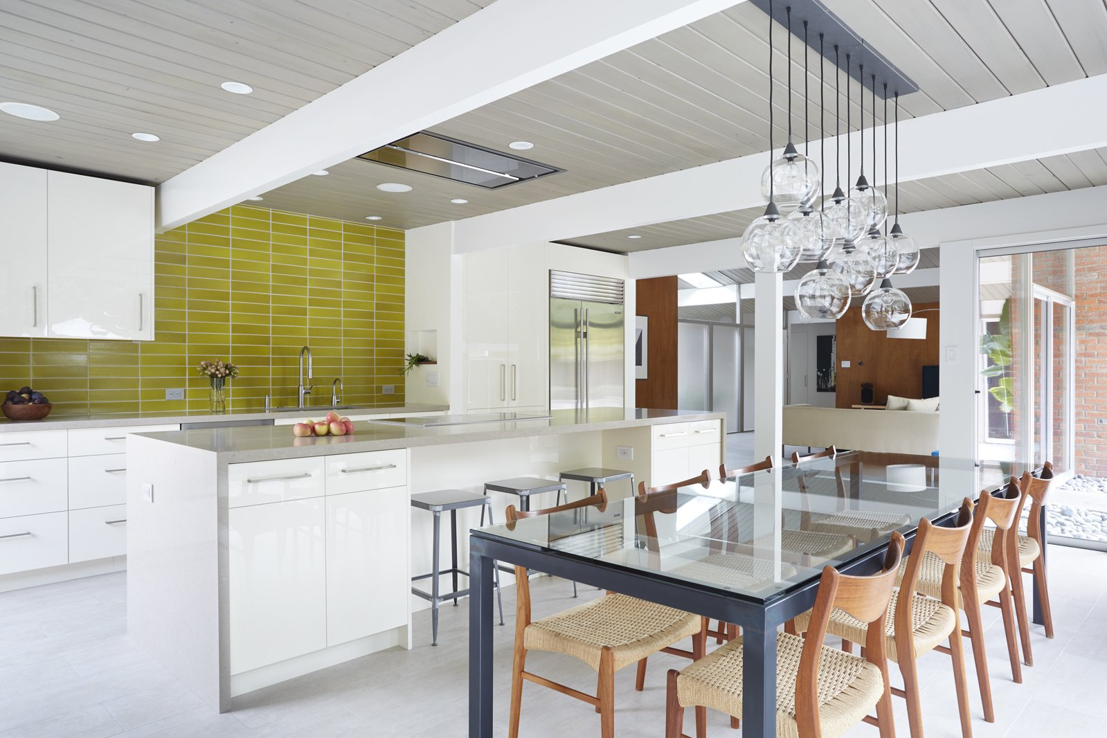 Renovated Eichler Kitchen and Dining Space Tagged: Kitchen, Engineered Quartz Counter, White Cabinet, Ceramic Tile Backsplashe, Pendant Lighting, and Refrigerator.  Photo 6 of 12 in How the Colors in Your Kitchen Affect Your Appetite from Northern California Eichler