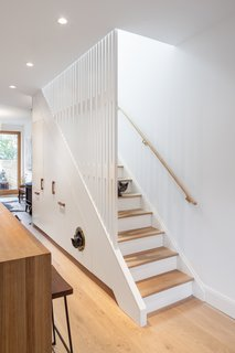 CAB Architects deftly hid appliances, pantry storage, and a litter box for the owners' two cats in the cabinetry beneath this staircase in Ritchie Rowhouse.