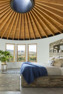 The ceiling of all three yurts is made with tongue-and-groove planks of Douglas fir that meet at a steel skylight at the center. A custom-made bed is complete with a linen duvet cover from Coyuchi and enticing sheepskin pillows.