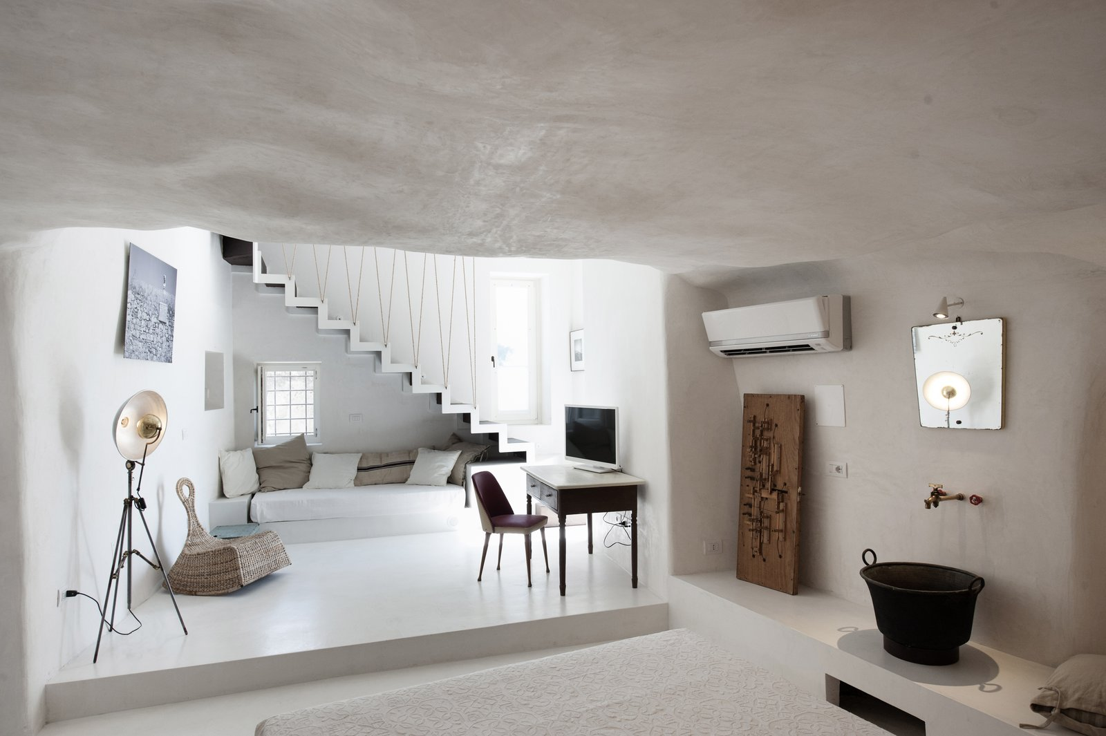 Living Room, Lamps, Chair, Floor Lighting, Bench, and Concrete Floor After relocating from Milan to the small Baroque town of Modica in Sicily, architect couple Marco Giunta and Viviana Haddad  purchased and restored an old house they found with locally sourced stones, tiles and plaster. They now operate it as Casa Talia – a boutique hotel where guests can experience life at a more leisurely pace.  Photo 6 of 11 in Ever Wanted to Stay in a Cave That's Actually Pretty Modern Inside?