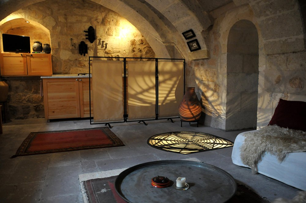 Bath Room, Limestone Floor, and Wall Lighting The three suites of Asmali Cave House in Cappadocia come with living rooms and kitchens, spacious bedrooms and unusual bathrooms.  Photo 10 of 11 in Ever Wanted to Stay in a Cave That's Actually Pretty Modern Inside?