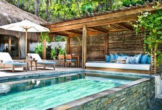 Nihiwatu is a cluster of luxury bale villas on Sumba, one of the more remote islands of Indonesia. Interiors are furnished with tropical hued fabrics, warm woods, rattan, soft drapery, and local artifacts.