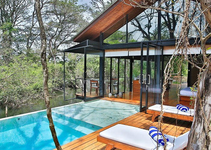Outdoor, Trees, Swimming Pools, Tubs, Shower, Wood Patio, Porch, Deck, Infinity Pools, Tubs, Shower, Decking Patio, Porch, Deck, and Small Pools, Tubs, Shower Situated in a former agricultural site that is now home to forest and wetlands, Kalundewa Retreat near the city of Dambulla marries with clean, modern lines with rustic teak and brick.  Photo 10 of 11 in Escape to the Jungle in One of These Modern Forested Retreats