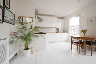 With white walls and wooden floors, subway tile backsplashes in the kitchen,  potted plants, and jungle-inspired wallpaper, this simple one-bedroom apartment is just a short walk from Hackney Central Overground Station and feels much larger than its actual size.