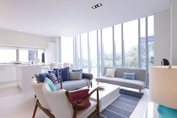 Decked out in plenty of white and cool grays and blues, this two-bedroom apartment sits in a luxury condominium in the heart of Singapore's city center. Its floor-to-ceiling windows in the living room offer immersive views of the city.