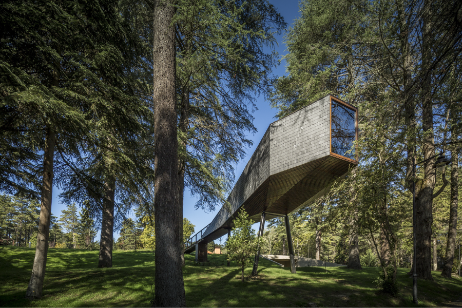 Part cabin, part tree house, and covered in slate and wood, Tree Snake House in Portugal's Pedras Salgadas Park was designed by architect Luís Rebelo de Andrade and has windows that offer prime views of the forest canopies and the stars in the night sky.  Photo 9 of 10 in Get Back to Basics by Staying at One of These Modern Cabins