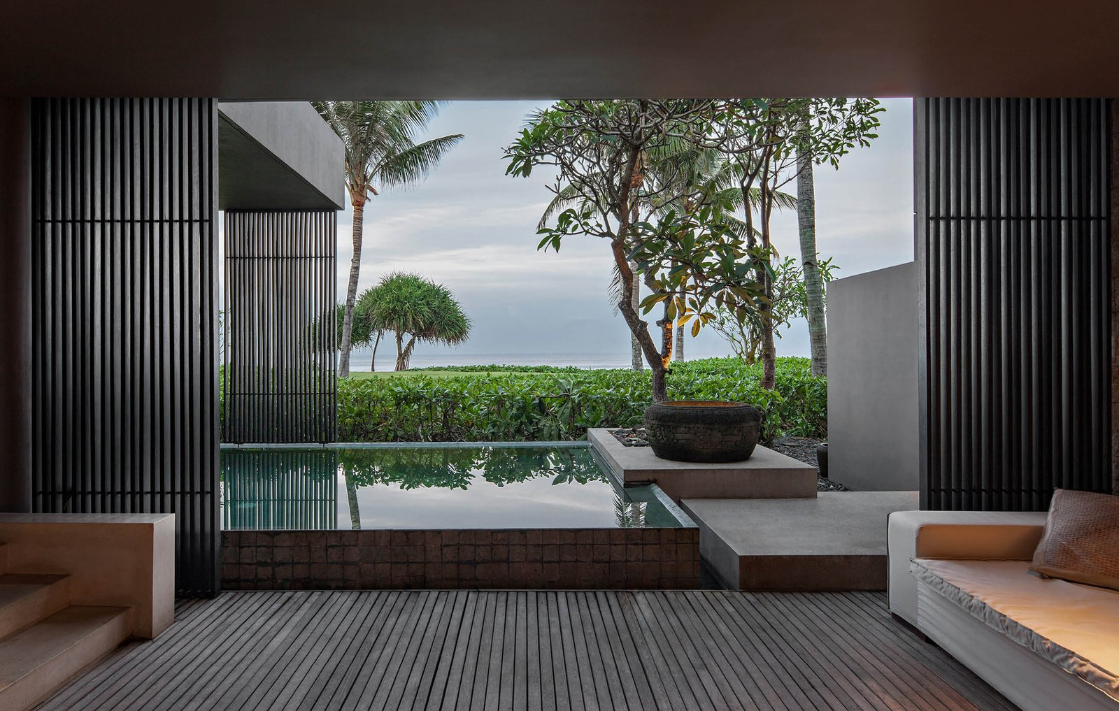 Outdoor, Trees, Infinity Pools, Tubs, Shower, Swimming Pools, Tubs, Shower, Large Pools, Tubs, Shower, Shrubs, Wood Patio, Porch, Deck, and Back Yard  Photo 6 of 9 in A Modern Bali Resort That's Inspired by the Local Landscape and Culture